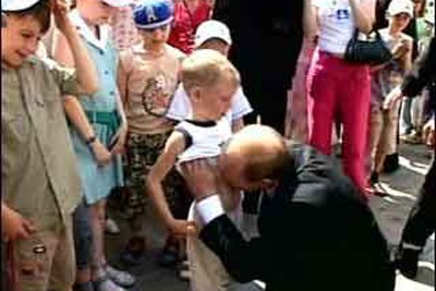 "No, you're not seeing things. That's really the then-""president"" of Russia Vladmir Putin lifting a little boy's shirt in broad daylight and kissing his stomach.  Note the reaction of the kid at the left.  Just one of many head-scratching moments from Tsar Putin, and nothing compared to Georgia."